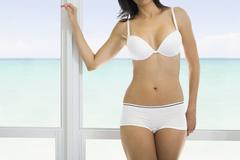 Hispanic woman standing at window Stock Photos