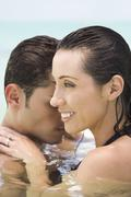 Hispanic couple hugging in water Stock Photos