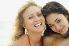 Smiling women standing on beach - stock photo