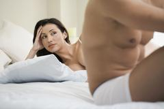Anxious woman looking at boyfriend on bed - stock photo