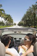 Hispanic couple driving in convertible - stock photo