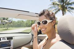Hispanic woman riding in convertible - stock photo