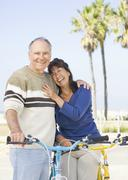 Couple walking bicycles on beach Stock Photos