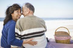 Couple having picnic on beach - stock photo