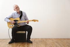 Caucasian man playing electric guitar Stock Photos