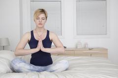 Caucasian woman meditating on bed Stock Photos