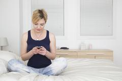 Caucasian woman using cell phone on bed Stock Photos