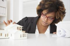 Stock Photo of African American businesswoman working on model of house