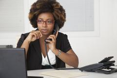 African American businesswoman working at desk Stock Photos