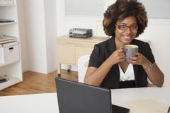African American businesswoman drinking cup of coffee at desk Stock Photos