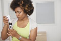 African American woman examining light bulb Stock Photos