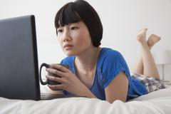 Chinese woman using laptop on bed Stock Photos