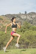 Hispanic woman running in rural field - stock photo