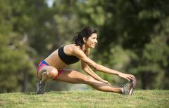 Hispanic woman stretching in rural field - stock photo