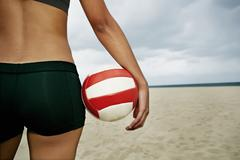 Mixed race woman holding volleyball on beach - stock photo