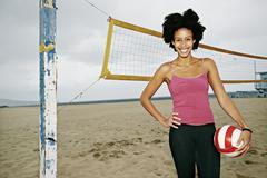 Mixed race woman holding volleyball on beach Stock Photos