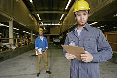 Caucasian workers with clipboards in warehouse Stock Photos