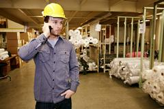Caucasian worker talking on cell phone in warehouse Stock Photos