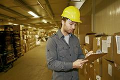 Stock Photo of Caucasian worker checking product in warehouse
