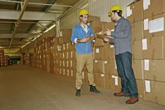 Caucasian workers talking in warehouse Stock Photos