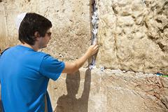 placing a note in the wailing wall - stock photo