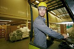 Caucasian worker driving machinery in warehouse Stock Photos
