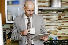 Hispanic businessman using tablet computer in kitchen Stock Photos