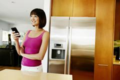 Stock Photo of Mixed race woman using cell phone in kitchen
