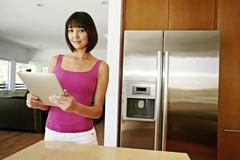 Mixed race woman using tablet computer in kitchen Stock Photos