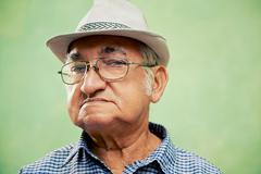 portrait of serious old man with hat looking at camera - stock photo