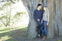 Smiling couple hugging in park - stock photo
