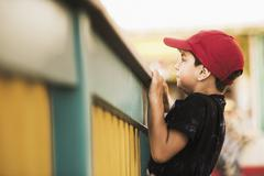 Mixed race boy climbing on banister - stock photo