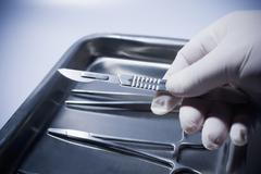 Stock Photo of Close up of Hispanic doctor holding surgical equipment
