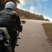 Man riding motorcycle on rural road Stock Photos