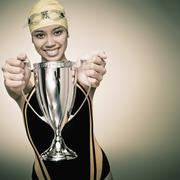 Mixed race swimmer holding trophy Stock Photos