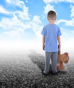 Lonley boy standing alone with teddy bear Stock Photos