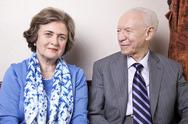 A high society senior couple (he's in his 80's, she's in her late 60's) sitti Stock Photos