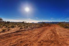Dirt road through desert Stock Photos