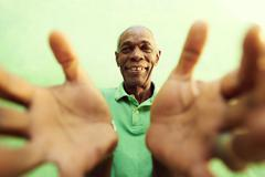 old african man with hands and arms open, embracing the camera - stock photo