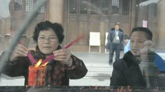 Chinese mature adult couple burn joss sticks in temple - stock footage