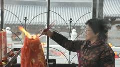 chinese mature adult woman burning joss sticks - stock footage