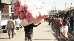 Man carrying high bundle of goods in open air market,  Addis Ababa,  Africa Stock Footage