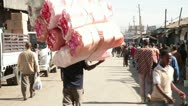 Stock Video Footage of Man carrying high bundle of goods in open air market,  Addis Ababa,  Africa