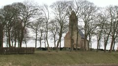 12th Century Church with graveyard on man-made mound Stock Footage