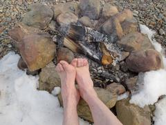 bare feet warming at a campfire in winter - stock photo