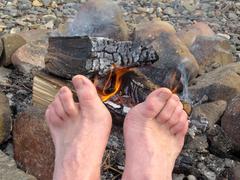 Bare feet warming at a campfire Stock Photos