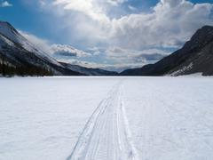 Well used winter trail on frozen mountain lake Stock Photos