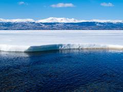 snowy mountains at frozen lake laberge, yukon, canada - stock photo