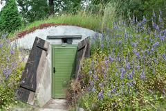 Underground dwelling under a blooming hill - stock photo