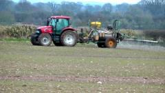 Tractor Spraying Fertilizer Onto A Crop Of Winter Wheat Stock Footage